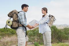 Hiking couple holding hands on mountain terrain - stock photo