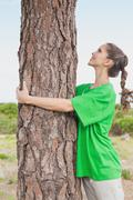 Stock Photo of Female environmental activist hugging tree trunk