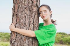 Female environmental activist hugging tree trunk Stock Photos