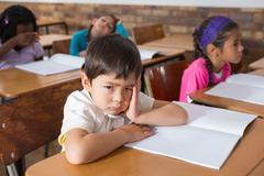 Bored pupil sitting at his desk - stock photo