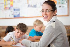 Stock Photo of Cute pupils writing at desk in classroom