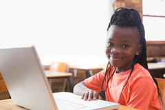 Cute pupil using laptop in classroom Stock Photos