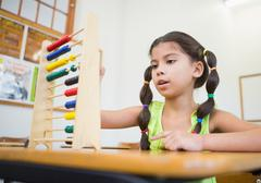 Stock Photo of Cute pupil using abacus in classroom