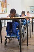 Disabled pupil writing at desk in classroom - stock photo