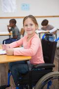 Disabled pupil smiling at camera in classroom - stock photo