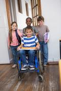 Disabled pupil with his friends in classroom - stock photo
