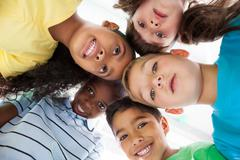 Stock Photo of Cute schoolchildren smiling at camera from above