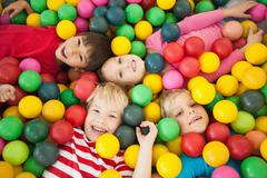 Happy children playing in ball pool - stock photo