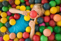 Happy boy playing in ball pool - stock photo
