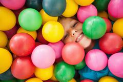 Stock Photo of Happy boy playing in ball pool