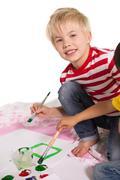 Happy little boy painting on the floor - stock photo
