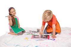 Happy little children painting on the floor Stock Photos