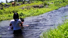 Children bathe in clear rocky spring river water Stock Footage
