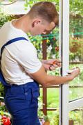 Man during window frame reparation Stock Photos