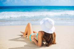 Woman relaxing on the beach Stock Photos
