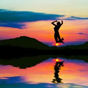 Silhouette of happy woman jumping at sunset Stock Photos