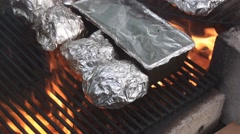 Grilling food in aluminium foil Stock Footage