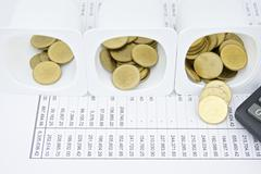 Gold coin difference amount in cup Stock Photos