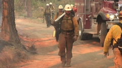 Stock Video Footage of Fire crew walking up mountain road with chain saw and tools and firetrucks