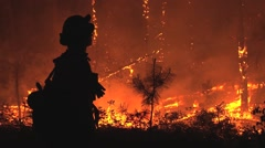 Silhouette of firefighter observing fire at night Stock Footage