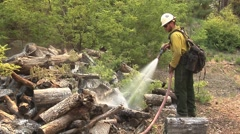 Firefighter hosing down wood pile to prevent burning Stock Footage