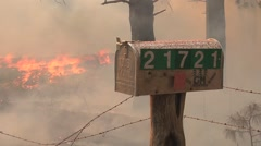 Heavy smoke and fire surround mail box on mountain road Stock Footage