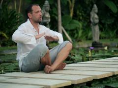 Young man doing breathing exercise in exotic garden NTSC Stock Footage