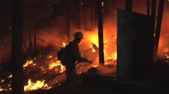 Firefighter hosing down outhouse to save it from the fire at night Stock Footage