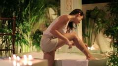 Woman shaving her leg in bathroom at night HD Stock Footage