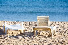 Two old sunloungers on tunisian beach Stock Photos