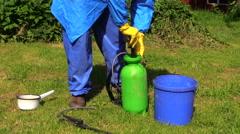 Hand mixed fertilizer in sprayer in green yard. Work in  garden. Stock Footage