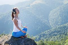 Stock Photo of young woman meditate on the top of mountain