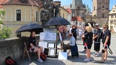 Prague. Man draws caricatures on a Charles bridge. - stock footage