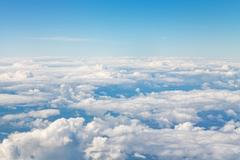 Horizon above white clouds in blue sky Stock Photos