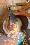 Grinding bench axe using a grinding machine Stock Photos