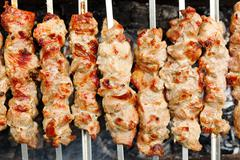 skewers with shish kebabs on brazier - stock photo