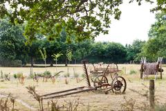 peasant household with abandoned farm equipment - stock photo