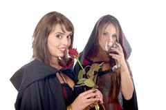 Two young women in disguise halloween with a glass of blood and a rose Stock Photos
