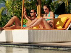 Couple on sunbeds applying sunscreen lotion on body by the pool NTSC Stock Footage