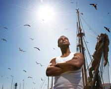 Handsome afro-american man against boat's mast. Kuvituskuvat