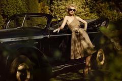Woman near a retro car outdoors Stock Photos