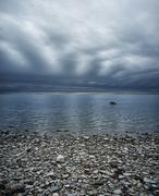 Stock Photo of moody sky over rocky beach