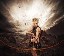 Woman archer against storm over rocks Stock Photos