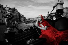 Beautifiul woman in red cloak riding on gandola Stock Photos