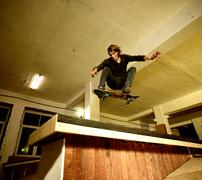 young man performing a stunt in a skatepark - stock photo