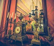 Antique clock and chandelier against mirror Kuvituskuvat