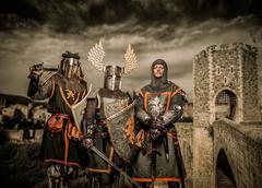 Three knight in armor against romanesque bridge over river , besalu Stock Photos