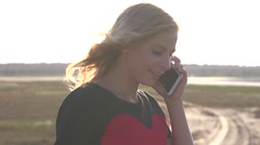 Young girl talking over her cell phone on nature Stock Footage