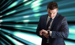 Composite image of handsome businessman checking the time - stock photo