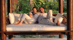 Happy young relaxed couple smiling to camera on gazebo bed HD Stock Footage